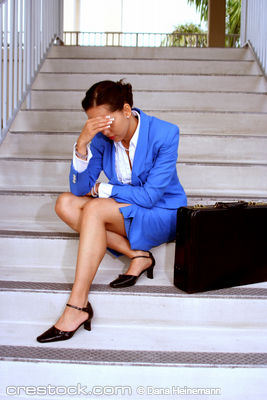 businesswoman sitting on stairs looking stress...